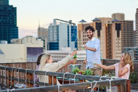 屋上テラスで屋外彼の友人の提案のお祝いに乾杯を作る男