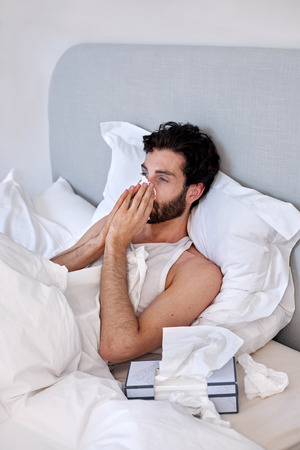 Tissues: depressed sad sick man with tissues in bed at home