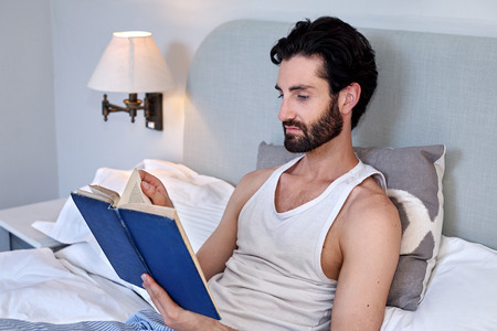 pjs: man relaxing on bed reading literature novel story book at home