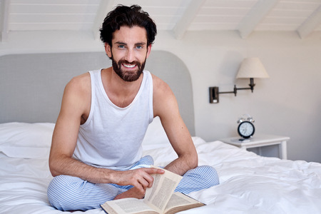 pj's: portrait of man relaxing on bed reading literature novel story book at home