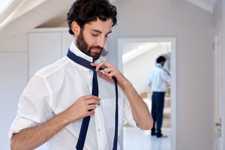'getting ready': professional man getting ready morning routine shirt and tie at home Stock Photo