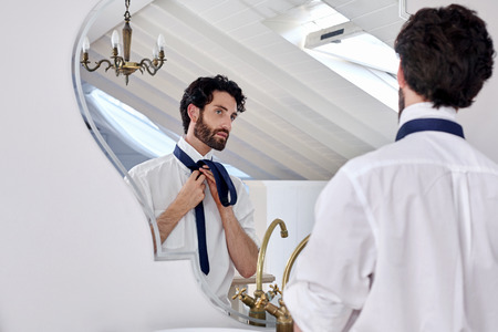 morning routine: professional man getting ready morning routine shirt and tie in mirror reflection at home Stock Photo