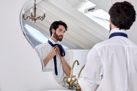 uomo professionale sempre pronto mattina camicia di routine e cravatta nella riflessione specchio a casa Archivio Fotografico