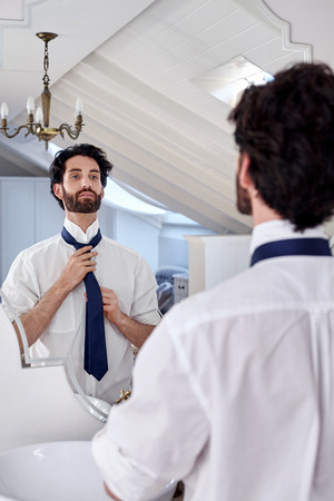 'getting ready': professional man getting ready morning routine shirt and tie in bathroom at home