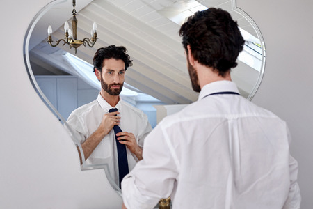 tie: professional man getting ready morning routine shirt and tie in bathroom at home
