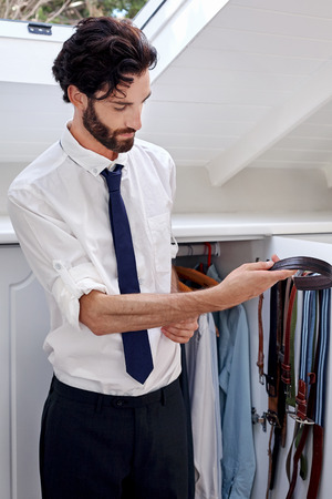 'getting ready': professional man getting ready for work choosing belt from bedroom cupboard