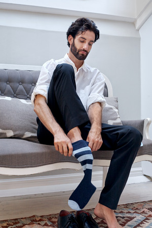 professional man getting ready for work putting socks for work in morning at home