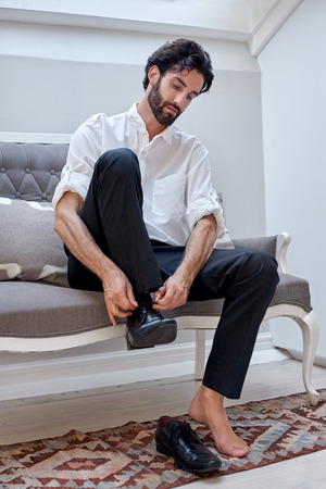 professional man getting ready for work putting smart shoes on and tying shoelaces at home Stock Photo