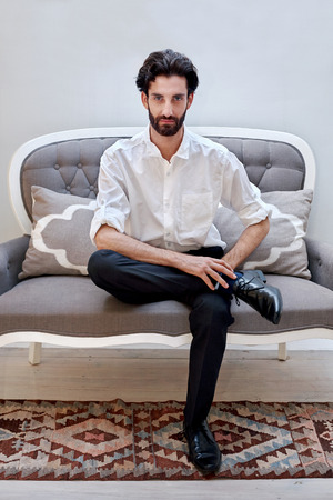 suave: portrait of serious handsome man sitting on a sofa couch chair at home