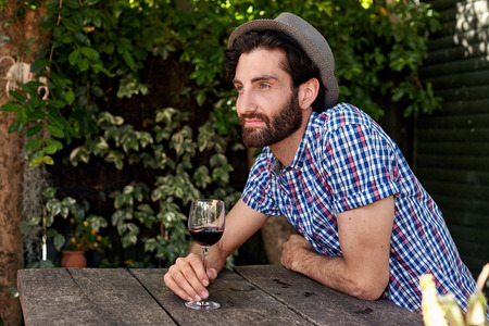 young man enjoying red wine outdoors in summer spring season backyard garden at home