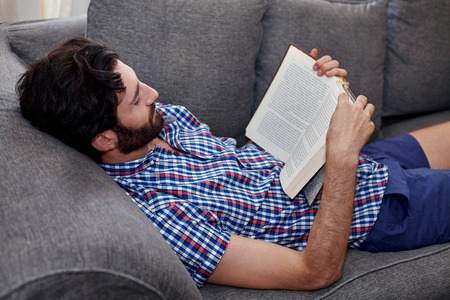 man holding book: man relaxing on sofa couch reading literature novel story book at home living room lounge
