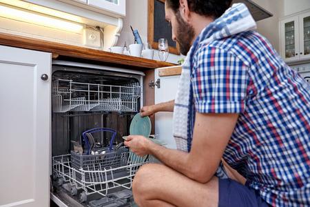 man packing dirty dishes into dishwashing machine in home kitchen