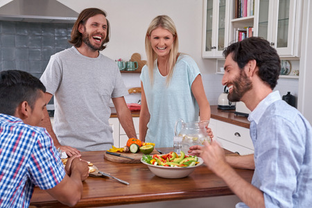 social gathering: group of friends laughing happy with salad in kitchen