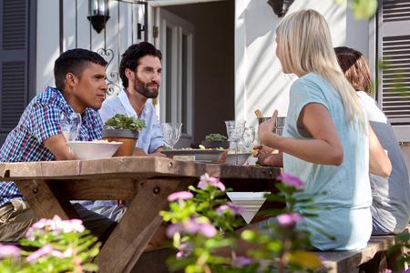 group of friends having outdoor garden dinner party