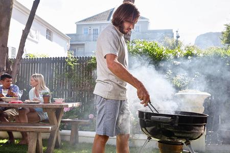 jonge man voorbereiden vuur voor vrienden barbecue tuinfeest Stockfoto