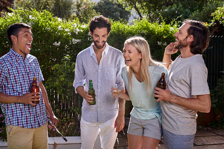 group of friends having outdoor garden party with alcoholic beer drinks Stock Photo