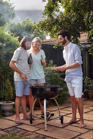 garden barbecue: man helping at the outdoor garden barbeque with a plate while man serves healthy chicken meat Stock Photo