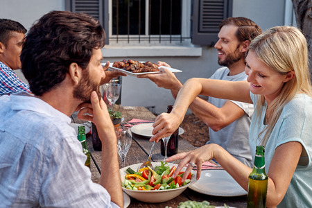 barbeque: group of friends having outdoor garden barbecue salad dinner with drinks