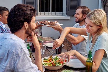 parrillero: grupo de amigos que tienen jardín barbacoa cena ensalada al aire libre con bebidas