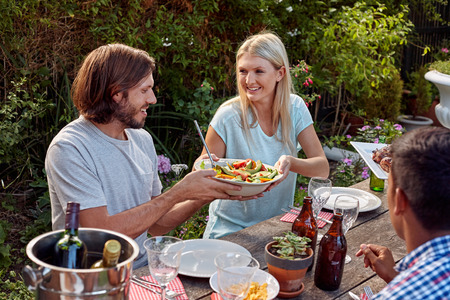 woman passing fresh healthy salad at outdoor friends dinner party gathering Banco de Imagens