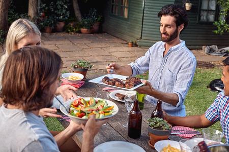 ドリンクとサラダの夕食を屋外ガーデン バーベキュー友人のグループ