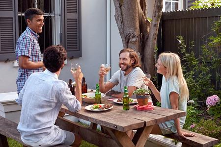 man toasting speech at friends outdoor garden party with wine drinks Standard-Bild