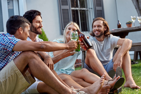 happy smiling diverse group of friends having outdoor garden party with beer wine drinks Standard-Bild