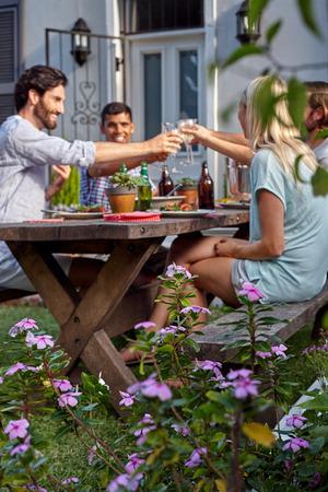 友達乾杯屋外の庭でワインの飲み物でお祝いするパーティのグループ 写真素材