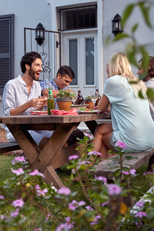 eating in the garden: group of friends having outdoor garden dinner party with drinks