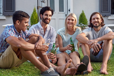 people sitting: happy smiling diverse group of friends having outdoor garden party with beer wine drinks Stock Photo