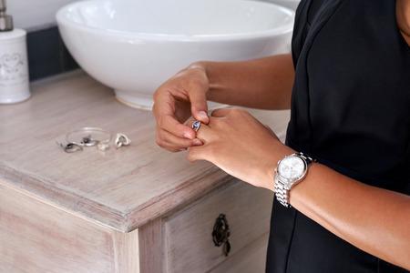 ジュエリー イヤリング時計朝早く自宅の浴室を持つ若いプロフェッショナルなビジネス女性 写真素材