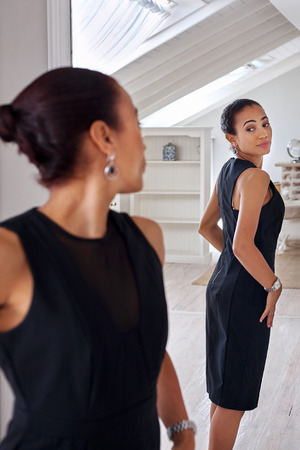 on mirrors: young professional business woman checking elegant dress in mirror reflection at home bedroom Stock Photo