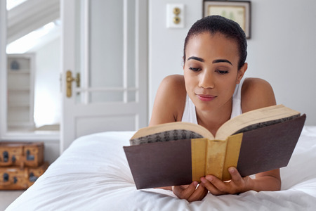 novel: young woman laying relaxing on bed reading literature novel story book at home