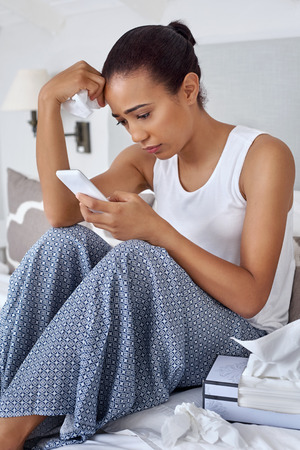 injured woman: depressed sad sick young woman with mobile cellphone tissues at home bedroom Stock Photo