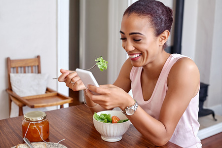 happy young woman enjoying healthy salad bowl with mobile cellphone at home kitchen