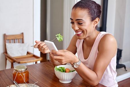 jovem feliz que aprecia a bacia salada saud�vel com telem�vel m�vel na cozinha de casa