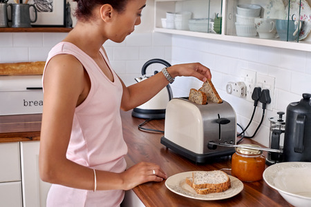 young woman making breakfast toast bread with toaster at home kitchen 스톡 콘텐츠
