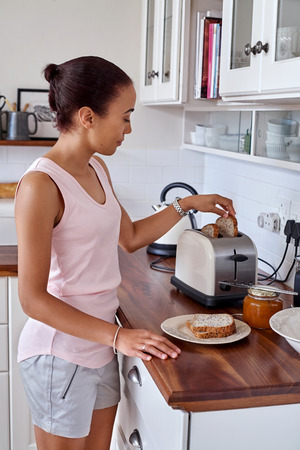 toaster: young woman making breakfast toast bread with toaster at home kitchen Stock Photo