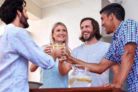 vaso de agua: amigos alegres jovenes que tuestan en el interior en la recolecci�n