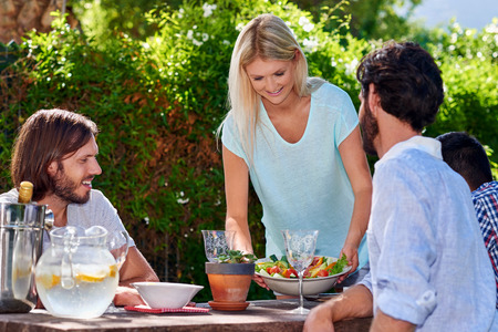 person appetizer: young woman serving salad to friends gathering at outdoor garden party