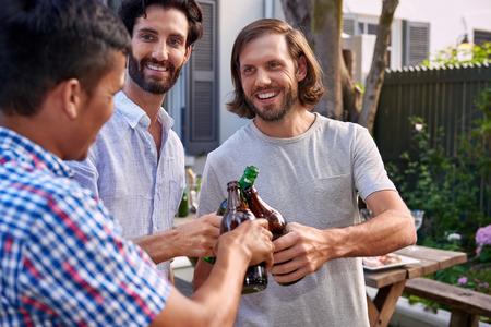 야외 정원 파티에서 알코올 맥주 병을 토스트 젊은 남자 환호