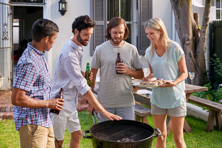 group of friends having outdoor garden barbecue with alcoholic beer drinks