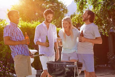 parrillada: grupo de amigos que tienen barbacoa en el jardín al aire libre riendo con bebidas alcohólicas cerveza Foto de archivo