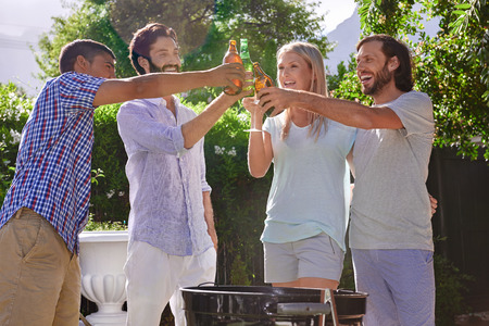 group of friends having outdoor garden barbecue laughing toasting with alcoholic beer drinks Stock Photo