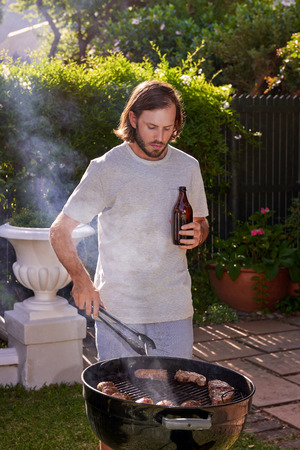 barbecuing: young man barbecuing tasty meat in outdoor garden with beer Stock Photo