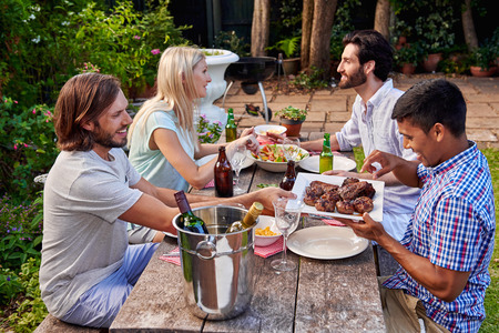 serving: group of friends having outdoor garden barbecue dinner with drinks Stock Photo