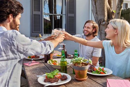 Gruppe von Freunden Toasten, um die Feier mit Getränken an Garten outdoors party