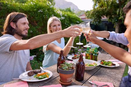 barbacoa: Grupo de amigos de tostado a la celebraci�n con bebidas en el jard�n al aire libre del partido