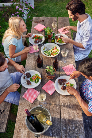skupina přátel, kteří požívají venkovní večeři