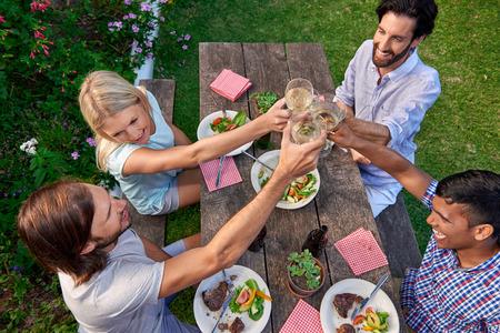 vino: Grupo de amigos de tostado a la celebraci�n con bebidas en el jard�n al aire libre del partido
